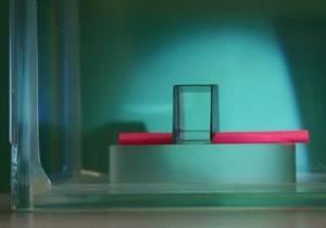 透明マントにより見えなくなったピンク色の紙を丸めた筒